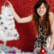 Young attractive woman decorating a small christmas tree — Stock Photo