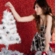 Stock Photo: Attractive young woman decorating a small christmas tree