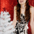 Young attractive woman decorating a small christmas tree — Стоковая фотография