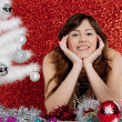 Young attractive woman with a small christmas tree and ornaments — Stock Photo