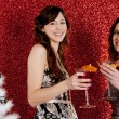Two young women drinking cocktails and having fun with a christmas tree — Stockfoto
