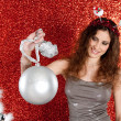 Attractive young woman holding an over sized Christmas bar ball — Stock Photo