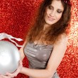 Attractive young woman holding a large christmas tree barball in the air — Stock Photo