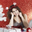 Young woman sitting at Christmas table surrounded by ornaments and gifts — ストック写真