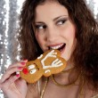 Young woman taking a bite off a Christmas raindear biscuit — Stok fotoğraf #22107169
