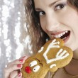 Stock Photo: Young attractive woman biting a Christmas decorated buiscuit.