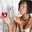 Attractive black woman using a Christmas barball reflection to apply her lipstick — Stock Photo