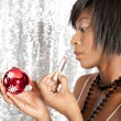 Attractive black woman using a Christmas barball reflection to apply her lipstick - Stock Photo