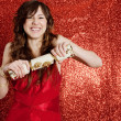 Young woman pulling a Christmas cracker — Stock Photo