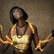 Attractive black woman dancing with Christmas lights — Stock Photo #22107505