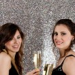Stock Photo: Two young women toasting with champagne glasses