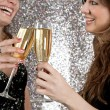 Stock Photo: Two young women toasting with champagne at a party