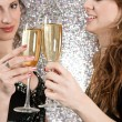 Two young women toasting with champagne at a party — Stock Photo #22107613