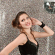 Attractive young woman dancing in a night club with a mirror ball  — Stock Photo