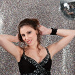 Attractive young woman dancing in a night club with a mirror ball — Stock Photo #22107635