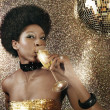 Stock fotografie: Attractive black woman in a nightclub drinking champagne