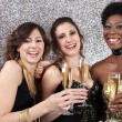 Three women toasting with champagne at a party — Stok fotoğraf