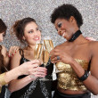 Three young women toasting with champagne at a party — Φωτογραφία Αρχείου