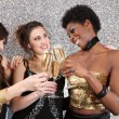 Three young women toasting with champagne at a party — Стоковая фотография
