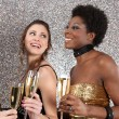 Foto Stock: Three women toasting with champagne at a party against