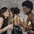 Three girls toasting with champagne at a party — Stok fotoğraf