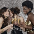 Three girls toasting with champagne at a party — Stockfoto