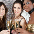 Three young women toasting with champagne at a party — Stock Photo