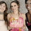 Three girls with a birthday cake and candles against a silver glitter background — 图库照片