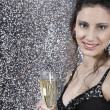 Girl holding a glass of champage against a silver glitter background — Foto de Stock