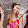 Three young women having a party and blowing whistles on each other — 图库照片