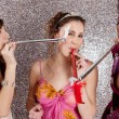Three young women having a party and blowing whistles on each other — Stock Photo