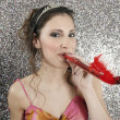 Young woman blowing a party blower while smiling — Stock Photo