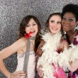 Foto Stock: Three young women having a party and blowing whistles