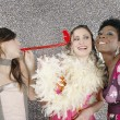 Three girls celebrating with party blowers — Stok fotoğraf