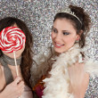 Two young women having a party dressing up and using a large candy to hide the face of one. — Stock Photo