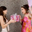 Young woman offering a gift to a birthday girl at a party — Stock Photo #22107915