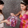 Young woman offering a gift to a birthday girl at a party. — Stock Photo