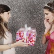 Girl giving a wrapped gift to her friend against a silver glitter background. — Stock Photo