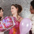 Three young women at a birthday party offering presents — Φωτογραφία Αρχείου