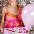 Young woman holding a wrapped gift and a pink balloon - Stock Photo