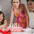 Three girls blowing the candles of a birthday cake at a party — Stock fotografie