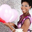 Attractive young black woman holding pink and red balloons — Stock Photo