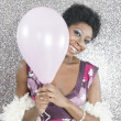 Royalty-Free Stock Photo: Young black woman holding a pink balloon and smiling at the camera