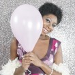 Young black woman holding a pink balloon and smiling at the camera - Stock Photo