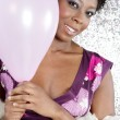 Attractive young black woman holding pink balloons against a silver glitter background - Stock Photo