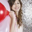 Young woman holding pink and red balloons — Photo