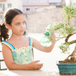Stock Photo: Young girl spraying water with a bottle onto a bonsai tree