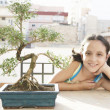 Portrait of a young girl with a bonsai tree in a busy city  — Stock Photo