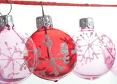 Small pink and red barballs Christmas tree ornaments hanging aligned on a red string — Stock Photo