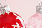 Two Christmas balls next to eather other agains a plain pink background. — Stock Photo